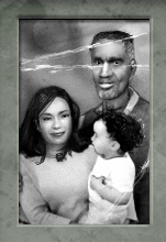 A black and white family portrait. Left is Azian, holding a baby Alyx on her left, placing her in the right of the image. Eli stands above and behind Alyx.